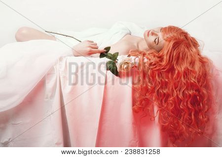 Sexy Redhead Girl With Rose In Hand Lies On White Bed Sheet, Long Red Hair Woman, Romantic And Gentl