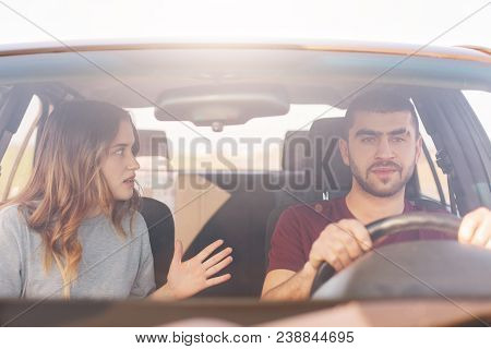 Terrified Female Gestures Actively And Tells Something Emotionally To Her Husband Who Drives Car And