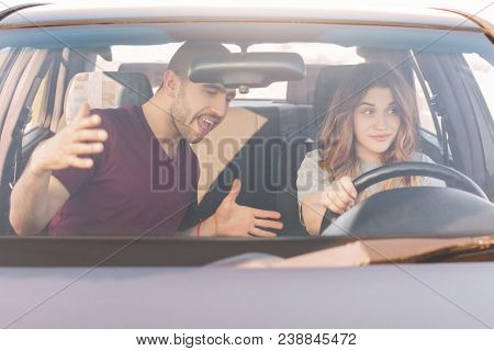 Driving Test. Male Instructor Teaches Inexperienced Female Trainee Drive Car, Controls Everything An