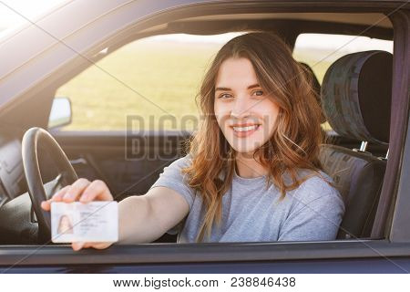 Smiling Young Female With Pleasant Appearance Shows Proudly Her Drivers License, Sits In New Car, Be