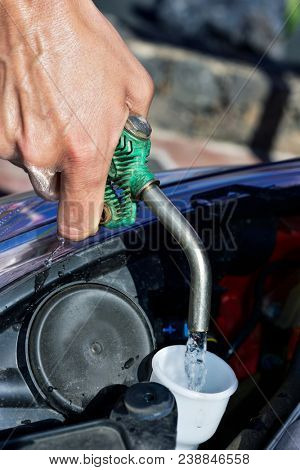 closeup of a young caucasian man filling the tank of windshield washer fluid of a car with water from a hosepipe