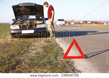 Car Breakdown Concept. Helpless Man Driver Stands Near Brocken Auto With Opened Hood, Has Problems W