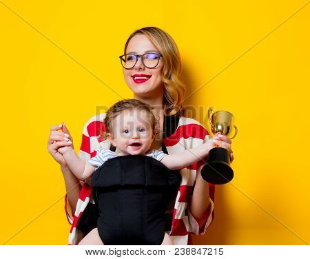 Little Baby In Carrier And Mother With Prize On Yellow Background