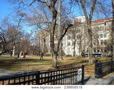 People Walking Their Dogs In Washington Square Park With Newberry Research Library In The Background