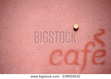 The Lettering Cafe On The Facade Of A Building In Color Contrasts To The Brighter Facade.