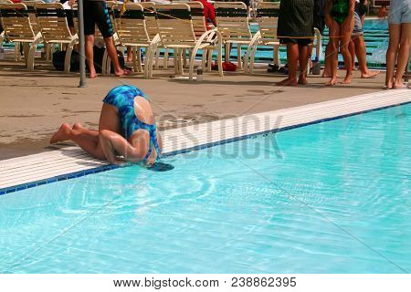 Humorous image of a girl in bathing suit cooling her head  in a