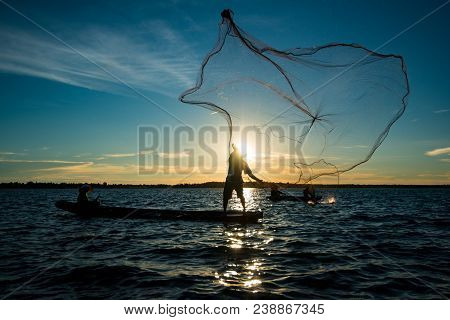 Un-identified Silhouette Fisher Man On Boat Fishing By Throwing Fishing Net To River During Sunset I