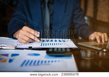 Close Up Businessman Consultant Holding Pen And Pointing At Financial On Wooden Desk In Coffee Shop.
