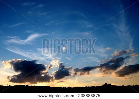 Beautiful Contrast Sunset View Of Twilight Ray With Blue Cloudy Sky And Silhouette Of Trees On Mount