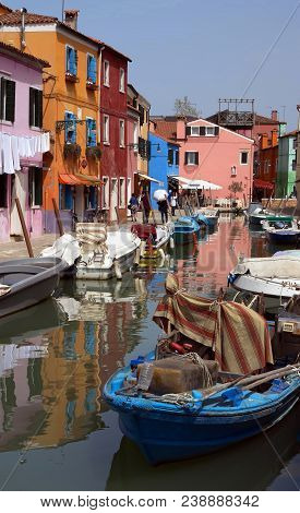 Venetian Island Of Burano. Street With Colorful Houses, Canal And Boats.