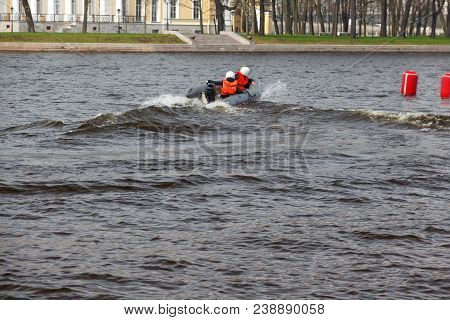 Two People Ride An Inflatable Boat With A Motor. Children's Water Competitions