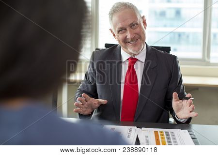 Tensed But Smiling Business Owner Negotiating With Sales Manager. Middle Aged Man In Formal Suit Wit