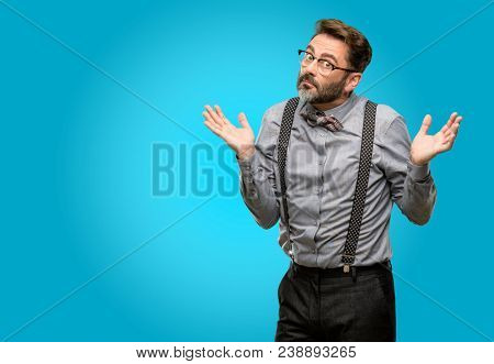 Middle age man, with beard and bow tie doubt expression, confuse and wonder concept, uncertain future shrugging shoulders