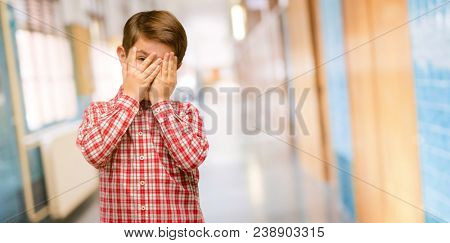 Handsome toddler child with green eyes smiling having shy look peeking through fingers, covering face with hands looking confusedly broadly at school corridor