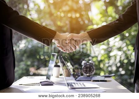 Two Business Man Shaking Hands During Meeting In Office With Blurred Garden Background, Business Peo