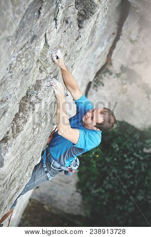 Male Rock Climber. Rock Climber Climbs On A Rocky Wall. Man Makes Very Hard Move And Tries To Fix On