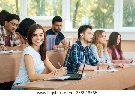 Young Student Looking At Camera Sitting In University Classroom With Her Groupmates On Background. S