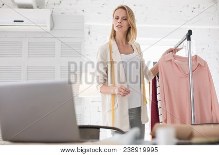 Target Audience. Ambitious Female Couturier Staring At Screen While Holding Garment