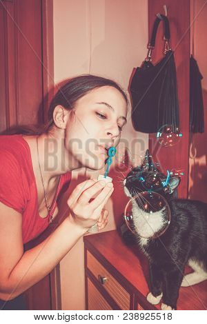 Retro Toned Image Of Girl With Soap Bubbles And Black And White Cat Interested In Them.