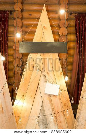 embellishment, design, illumination concept. there are wooden mountains collected of long boards, lots of lights decorate these elements of interior placed by the wall poster