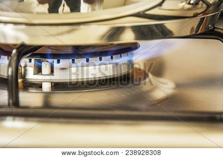 Focus Of Blue Flame Gas On A Cooker Boiling Pot In Kitchen Gas Stove. Cooking Food.