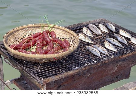 Seaside Grill With Saltwater Fishes And Pork Sausages. Fish And Meat Grill By Sea. Seaside Lunch Wit