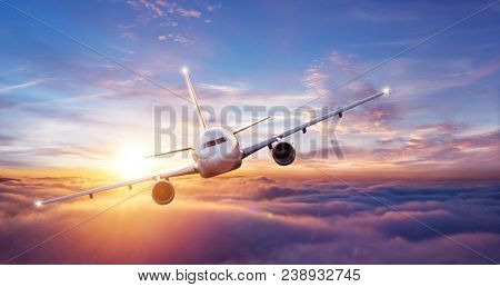 Passengers commercial airplane flying above clouds, front view. Concept of fast modern travel