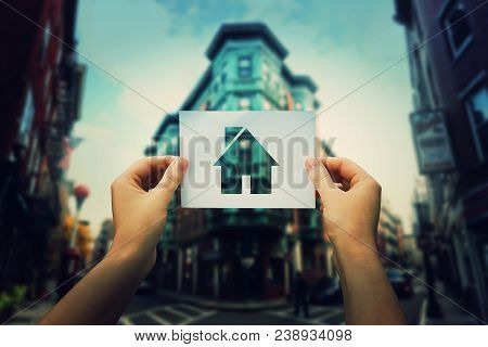 Woman Hands Holding A Paper Sheet With House Icon Inside In The Middle Of The Street Of A Big City.