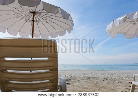 Lounge Chairs With Sun Umbrella On A Beach. Sun Of Summer Time On Sky And Sand Of Beach Relaxation L