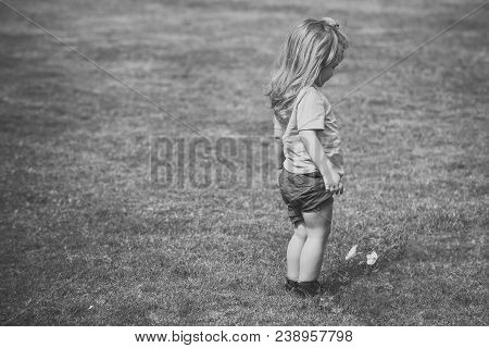 Boy Small Cute Kid With Blond Long Hair In Green Shirt And Blue Shorts Standing And Looking At Littl