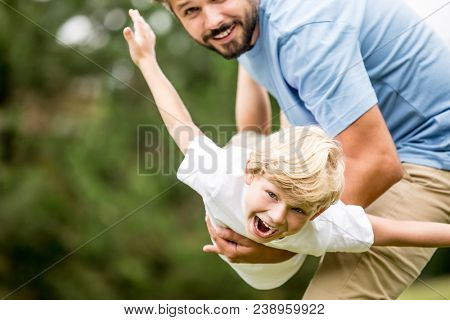 Boy with vitality laughing with joy playing with father at the park