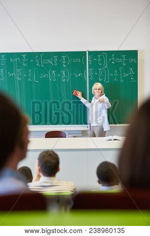 Woman as teacher in math class using chalkboard for lecture