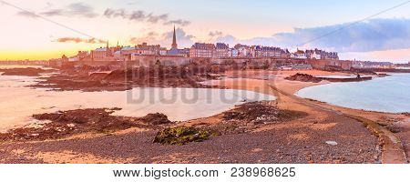 View from the tidal island of Grand Be to the city of Saint Malo and causeway shortly before the tide at sunrise. Saint-Maol is famous city of Privateers is known as city corsaire, Brittany, France. poster