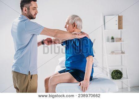 Side View Of Rehabilitation Therapist Doing Massage To Senior Man On Massage Table