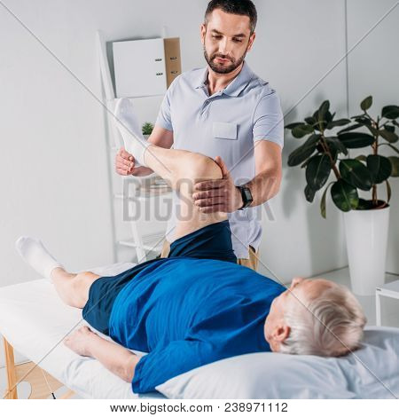 Focused Rehabilitation Therapist Massaging Senior Mans Leg On Massage Table