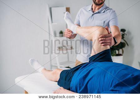 Partial View Of Rehabilitation Therapist Massaging Senior Mans Leg On Massage Table