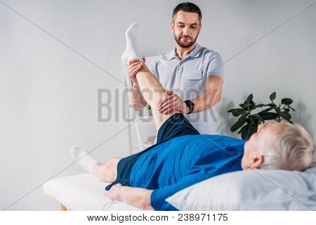 Portrait Of Rehabilitation Therapist Massaging Senior Mans Leg On Massage Table