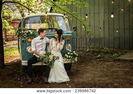 Cheerful Happy Young Couple Sit On The Bumper Retro-minibus