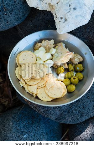 Cheese, Fish, Olives, And Crackers From A Fresh Catch Cooked And Salted For Preservation While Backp