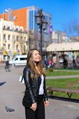 Young female person walking in city and wearing leather jacket. Concept of strolling and spring weather. poster