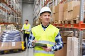 logistic business, shipment and people concept - smiling male worker or supervisor with clipboard in reflective safety vest at warehouse poster