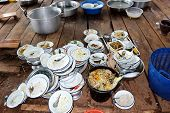 Plate, bowl, spoon. Have not washed. Are stack on wooden board. Food waste stuck. Have a full tank of food waste. Basin, casserole, mortar, blue basket and small wooden chair put all around. poster