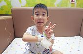 Admitted sick kid patient victory symbol on saline bandage hand feel happy at hospital with medical treatment poster