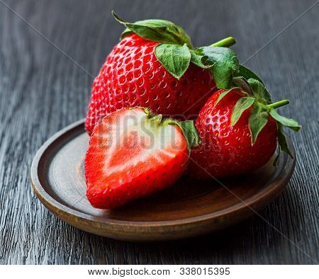 Fresh Red Strawberries In Ceramic Bowl On Rustic Wooden Table Background. First Harvest Of Ripe Stra