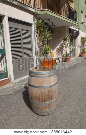 Vernazza, Italy - April 2 2018: The View Of The Huge Glass Of Aperol Spritz On A Typical Street In V