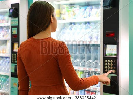 Young Traveler Woman Choosing A Snack Or Drink At Vending Machine In Airport. Vending Machine With G