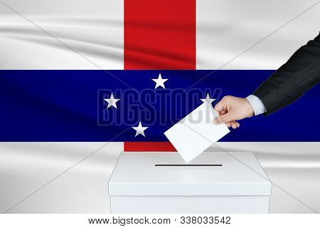 Election In Antilles. The Hand Of Man Putting His Vote In The Ballot Box. Waved Antilles Flag On Bac