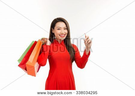 Asian Woman In Ao Dai Traditional Red Dress Holding Shopping Bag And Paid Via Credit In Lunar New Ye