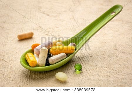 vitamins and supplements - pills and capsules and tablets on a Chinese ceramic spoon, healthcare, self care and wellbeing concept