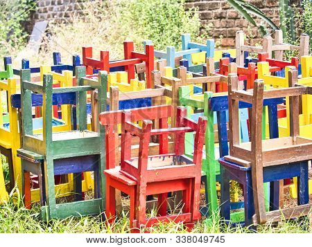 Stack Of Assorted Colored Wooden Chairs In Random Disarray, Full Frame Furniture Background Image